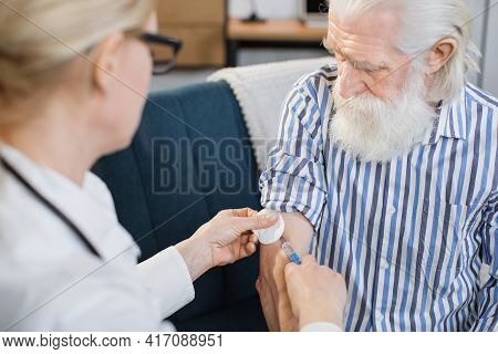 View From The Shoulder Of Female Professional Doctor. Senior Bearded Man, Is Vaccinated At Home By H