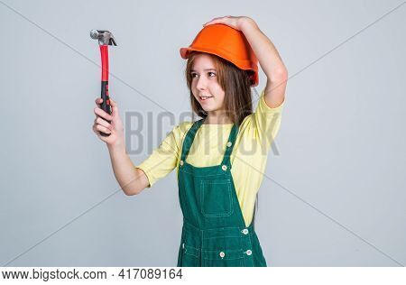 Teen Girl Laborer In Protective Helmet And Uniform On Grey Background Use Hammer, Worker