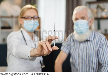 Blurred View Of Woman Doctor And Senior Man Patient, In Protective Masks, Sitting Together On The Co