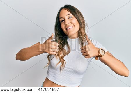 Young brunette woman wearing casual white t shirt success sign doing positive gesture with hand, thumbs up smiling and happy. cheerful expression and winner gesture.