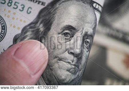 A Man Holding A One Hundred Dollar Bill In His Hand. Close Up.