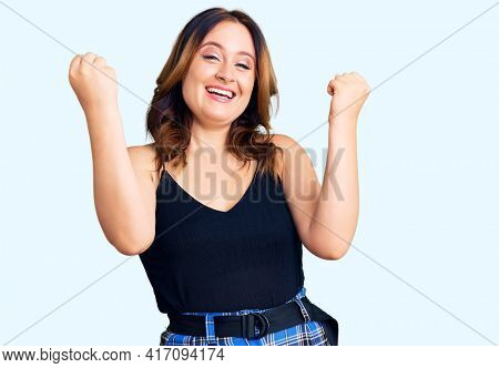 Young beautiful caucasian woman wearing casual clothes screaming proud, celebrating victory and success very excited with raised arms