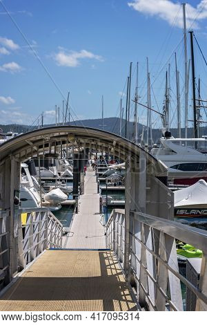 Airlie Beach, Queensland, Australia - April 2021: Floating Marina Walkway Out Onto Pontoons Where Bo