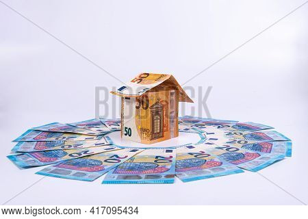An Abstract House Of 50 Euro Banknotes In The Middle Of A Circle Of 20 Euro Banknotes, Close-up