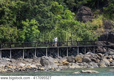 Airlie Beach, Queensland, Australia - April 2021: Elderly Man And Woman Walking Along Wooden Elevate