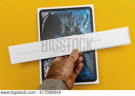Paris, France - Nov 16, 2018: Male Hand Holding Cardboard Package Of New Apple Pencil Above The Late