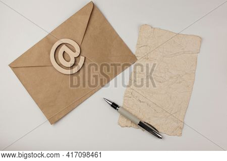 An e-mail sign on a brown envelope with blank crumpled old paper sheet lies on a white background. Concept e-mail message letter. Top view
