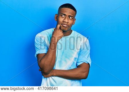 Young black man wearing tye die t shirt serious face thinking about question with hand on chin, thoughtful about confusing idea