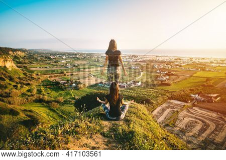 Woman Practices Yoga And Meditates In Easy Pose On The Top Of The Mountain At Sunset. Soul Leaves Bo