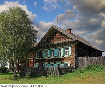 View Of The Historical Traditional Wooden House With Carved Windows And Birch Tree In Front Of It. R