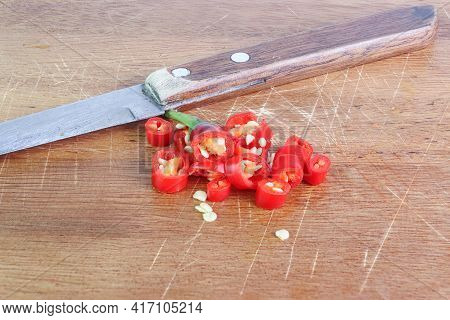 Chili - The Red Pepper With Cutting A Chili Pepper On Wood