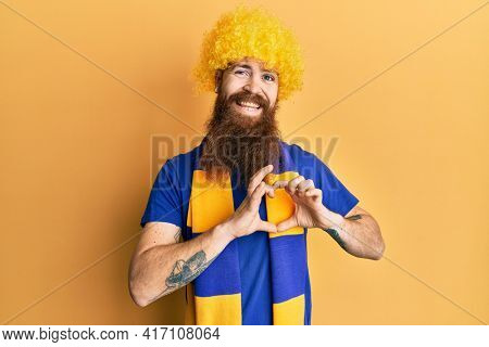 Redhead man with long beard football hooligan cheering game wearing funny wig smiling in love doing heart symbol shape with hands. romantic concept.