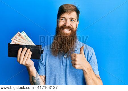 Redhead man with long beard holding wallet united kingdom pounds smiling happy and positive, thumb up doing excellent and approval sign