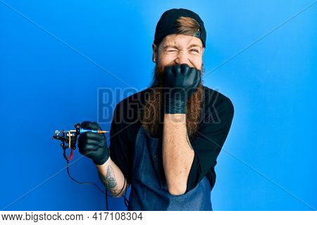 Redhead man with long beard tattoo artist wearing professional uniform and gloves laughing and embarrassed giggle covering mouth with hands, gossip and scandal concept