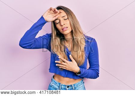 Beautiful hispanic woman wearing casual blue shirt touching forehead for illness and fever, flu and cold, virus sick