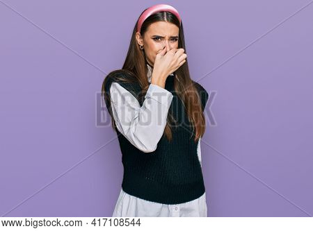 Young beautiful woman wearing casual white shirt smelling something stinky and disgusting, intolerable smell, holding breath with fingers on nose. bad smell