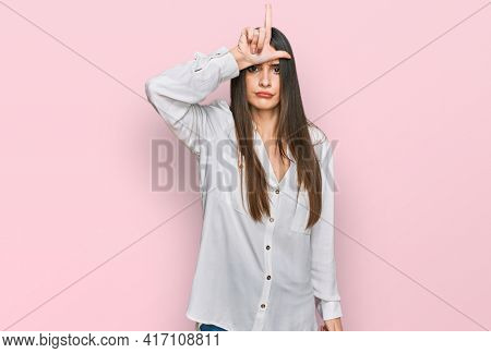Young beautiful woman wearing casual white shirt making fun of people with fingers on forehead doing loser gesture mocking and insulting.