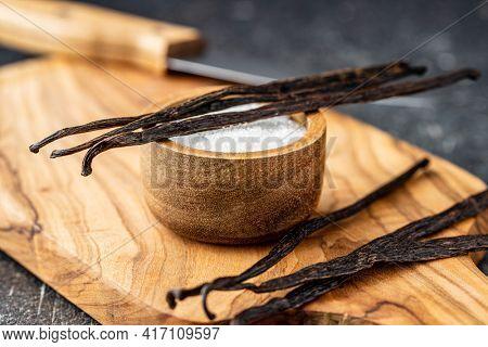 Vanilla pods. Sticks of vanilla and white sugar on cutting board.
