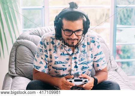 Latino Man Sitting On The Sofa, Playing Video Games. He Has Headphones And Controller. Technology Co