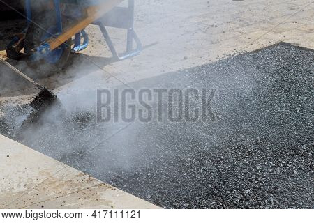 Road Worker Repair Asphalt Covering New Road Surface While Laying Asphalt