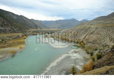 A Winding Bed Of A Beautiful Turquoise River Flowing In Early Autumn Through A Canyon In A Valley Su