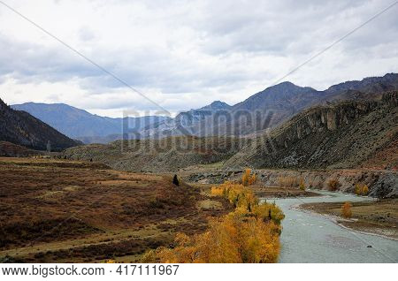 A Calm Mountain River Flows Through A Valley Covered With Coniferous Forest In Early Autumn, Surroun