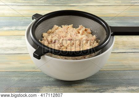 Rinsed Canned Albacore Tuna Draining In Strainer Into White Bowl