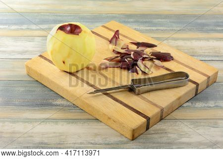 Peeling Red Delicious Apple On Wooden Cutting Board With Peels And Peeler Kitchen Utensil