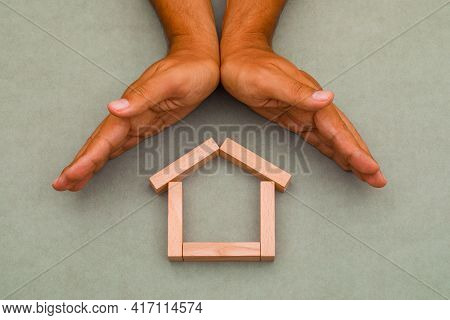 Mortgage Concept On Greenish Grey Background Flat Lay. Hands Enclosing Wooden House.