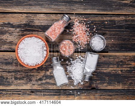 Some Sea Salt And Himalayan Salt In Bowls And Coming Out Of Salt Shakers On Dark Wooden Background,