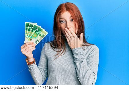 Young red head girl holding 50 israel shekels banknotes covering mouth with hand, shocked and afraid for mistake. surprised expression