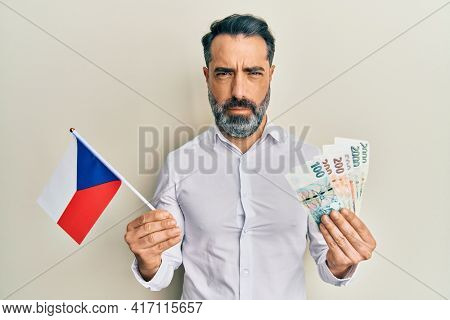 Middle age man with beard and grey hair holding czech republic flag and koruna banknotes skeptic and nervous, frowning upset because of problem. negative person.