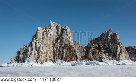 A Picturesque Double-headed Rock Rises Above The Ice Of A Frozen Lake Against The Backdrop Of A Clea