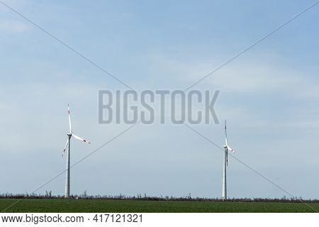Group Of Low Angle View Of Wind Turbine Towers Again Cloudy Blue Sky At The Wind Farm. Green, Sustai