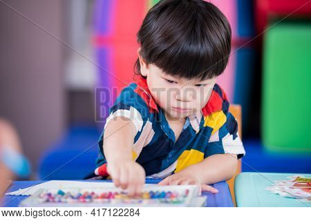 Adorable Asian Boy Reached For Pick Up Chalk Paint, Baby Made Art On The Paper Placed On The Table.