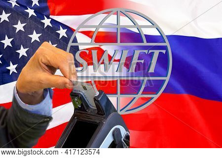 Flag Of Usa And Russia Flag And Text Of Swift. Hand Of Woman With Credit Card In Payment Terminal. S