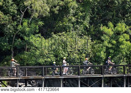 Airlie Beach, Queensland, Australia - April 2021: Adults And Children Riding Bikes On Timber Walkway