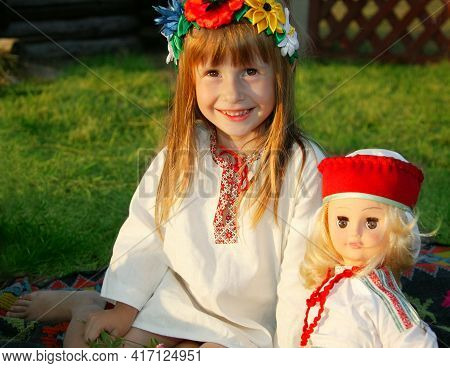 Little Ukrainian Or Belarusian Girl In National Clothes With An Ethnic Doll.