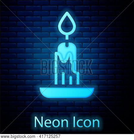 Glowing Neon Burning Candle Icon Isolated On Brick Wall Background. Cylindrical Candle Stick With Bu