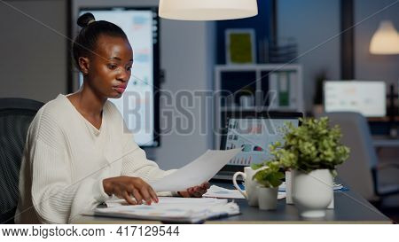 Black Manager Analysing Graphics And Financial Statistics From Documents