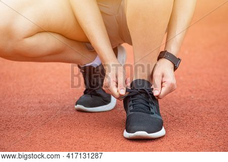 Close Up Of Runner Woman Tying Shoelaces. Conceptual Of Woman Getting Ready For Jogging In The Runni