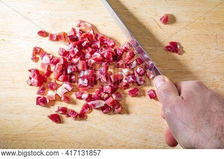 Iberian Ham (serrano) Cut Into Cubes (diced). Hand Cutting On Wooden Board.