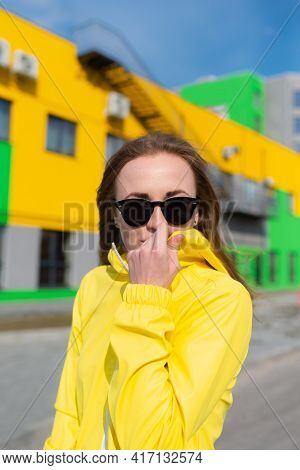 A Young Woman Embracing The Cold Spring Weather Snuggling Into Her Warm Yellow Jacket Strolling Alon