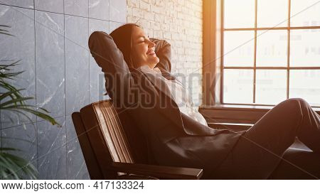 Delighted Businesswoman With Short Dark Hair Sits Down Falling On Brown Bench With Happy Smile In Of