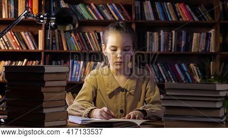 Exhausted Young Lady Writes Home Assignment In Copybook With Brown Pencil Sitting Among Different Bo