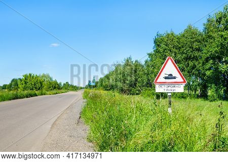 Traffic Sigh 'caution Tanks' In Country Side. Writing Translates As 'caution Tanks'. Writing On Far