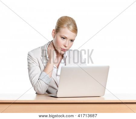 Tired young businesswoman sitting at a office desk with laptop, isolated