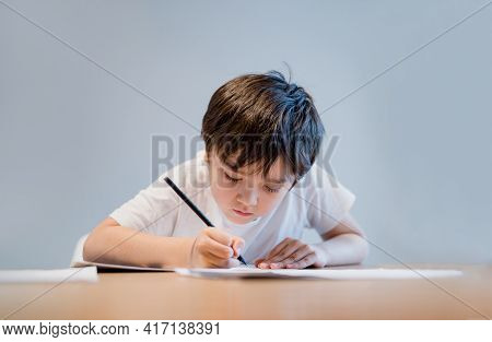 Kid Holding Pencil Writing On White Paper, Child Boy Is Drawing, Portrait Of School Kid Doing Homewo