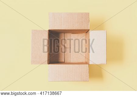 One Empty Open Cardboard Box On Pastel Yellow Background. Top View, Copy Space