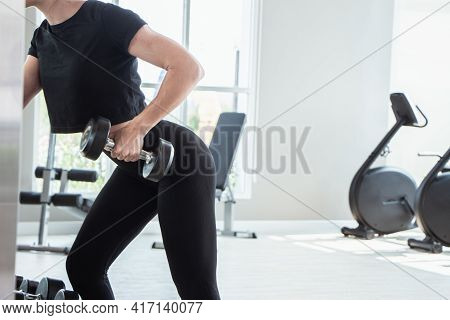 A Beautiful Caucasian White Woman Holding A Body Dumbbell Standing In Front Of A Mirror At A Fitness